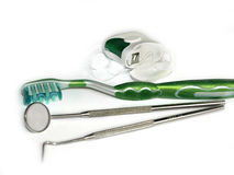 Toothbrushes, dental floss and a mirror on white Royalty Free Stock Photos