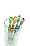 Toothbrushes in a glass. Four colored toothbrushes in a glass closeup on a white background Royalty Free Stock Photography