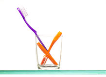 Toothbrushes in glass. Two toothbrushes in glass, one split in half; isolated on white background Stock Images