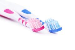 Toothbrushes, his and her's. Close-up shot of red and blue toothbrush isolated on white background Stock Images
