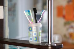 Toothbrushes in a plastic cup. One brush stands out. Black toothbrush. Close up.  stock photos