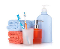 Toothbrushes, shampoo bottles and two towels Stock Images