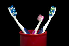 Toothbrushes. Three toothbrushes in a glass of red on a black background isolated Royalty Free Stock Photography