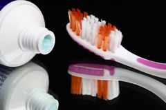 Toothbrushes and toothpaste on a mirror shelf. Oral hygiene products royalty free stock photo