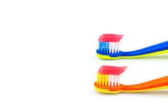 Toothbrushes with toothpaste. Toothbrushes with pink toothpaste isolated on white background Royalty Free Stock Image