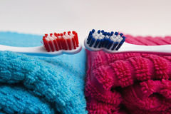 Toothbrushes, towels on color Stock Photos