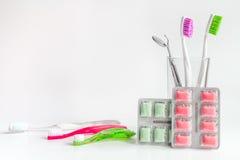 Toothbrushes w szkle na białych tło narzędziach dla oralnej opieki Zdjęcia Stock