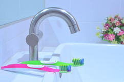 Toothbrushes at white wash basin Royalty Free Stock Image