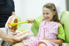 toothbrushing模型的牙医椅子的女孩 库存照片
