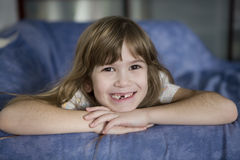 Toothless cute smiling seven year girl. Closeup portrait toothless cute smiling girl with long hair Royalty Free Stock Photos