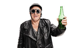 Toothless senior biker holding a bottle of beer. Toothless senior motorcyclist in black leather jacket and goggles holding a bottle of beer and looking at the Royalty Free Stock Images