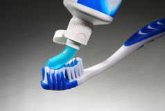Toothpaste. Putting toothpaste on a brush Royalty Free Stock Photos