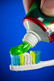Toothpaste being squeezed onto a toothbrush Royalty Free Stock Photo