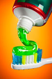 Toothpaste being squeezed onto a toothbrush Royalty Free Stock Images