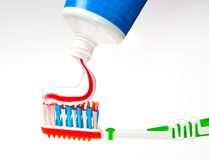 Toothpaste being squeezed onto  toothbrush Royalty Free Stock Image