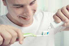 Toothpaste and toothbrush. The guy squeezes toothpaste on the toothbrush stock image
