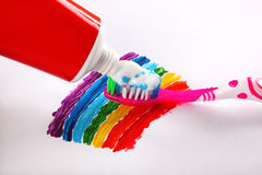 Toothpaste and toothbrush on rainbow background Stock Photos