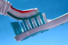 Toothpaste on toothbrush. Squeezing striped toothpaste onto wet toothbrush on blue background Stock Photo
