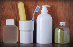 Toothpaste, toothbrushes, soap, aftershave on bathroom shelf Stock Images