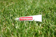 Toothpaste tube in green grass. White tube of toothpaste in green grass outside Stock Images