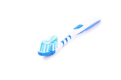 Toothpate on a toothbrush. Close-up shot of a toothpaste on a blue toothbrush  on white background Royalty Free Stock Image