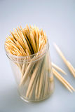 Toothpicks in a container. Close-up of wood toothpicks in a plastic container. Few sticks lying near the container. Shallow DOF Stock Image