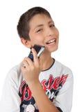 Toothy de glimlachen en het scheren van de jongen wang met scheerapparaat Royalty-vrije Stock Fotografie