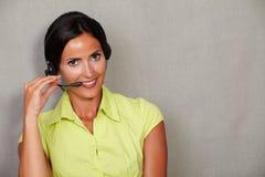 Toothy glimlachende receptionnist die op hoofdtelefoon spreken stock foto