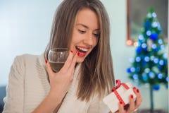 Toothy glimlachende vrouw die met rode lippen giftdoos en wijnstokglas houden Glimlachende jonge vrouw in een feestelijke kleding Stock Afbeelding