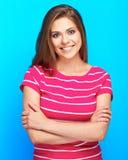 Toothy glimlachende vrouw in roze kleren die zich over blauwe backgro bevinden royalty-vrije stock foto's