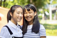 Toothy het glimlachen gezicht van Aziatische tiener twee status openlucht stock afbeeldingen