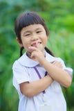 Toothy le lyckaframsida av asiatiska barn mot gräsplan bl Arkivbild
