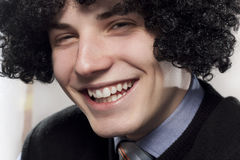 Toothy Smile. Portrait of young man with curly hair Royalty Free Stock Photos