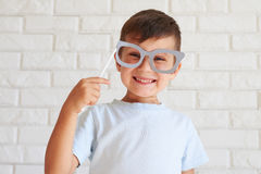 Toothy smile boy holding paper moustache having fun Stock Image