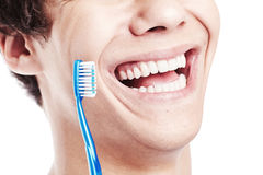 Toothy smile with brush closeup. Close up of young man holding toothbrush near his toothy smile with perfect healthy white teeth isolated on white background Royalty Free Stock Photo