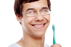 Toothy smile with brush closeup. Face close up of young hispanic man wearing glasses holding toothbrush near his toothy smile with perfect healthy white teeth Royalty Free Stock Photos