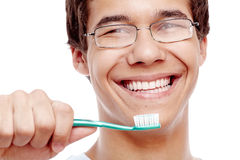 Toothy smile with brush closeup. Face close up of young hispanic man wearing glasses holding toothbrush near his toothy smile with perfect healthy white teeth Stock Photo