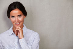 Toothy smile businesswoman with hand on chin. Toothy smile businesswoman in formalwear with hand on chin while looking at camera on grey texture background Stock Photo