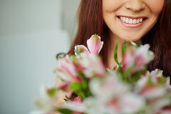 Toothy smile. Close-up of female toothy smile and flowers Royalty Free Stock Photo