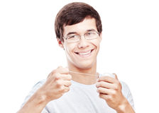 Toothy smile with dental floss. Close up of young hispanic man wearing glasses holding dental floss near his toothy smile with perfect healthy white teeth Royalty Free Stock Photo