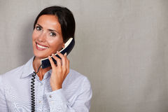 Toothy smile lady speaking on phone. Toothy smile lady speaking on the phone in button down shirt while looking at camera on grey texture background Royalty Free Stock Images