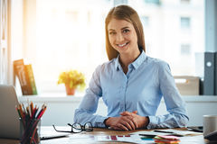 Toothy smile from real expertise. Cheerful young beautiful woman looking at camera with smile while sitting at her working place Royalty Free Stock Photography