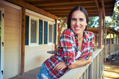 Toothy smile of relaxed woman who is leaning on the handrail near the wooden rest house. Close-up side shot of a toothy smile of relaxed woman who is leaning on royalty free stock photo