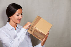 Toothy smile woman standing and opening parcel. In formal clothing on grey texture background Stock Image