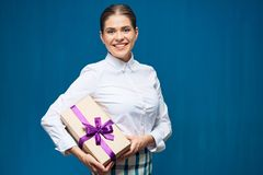 Toothy smiling business woman holding gift box. Isolated portrait on blue Royalty Free Stock Photo