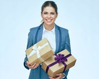 Toothy smiling business woman standing with gift box against whi. Te background. Isolated portrait. Business suit Stock Photo