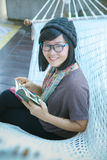 Toothy smiling  face of asian reader woman and pocket book in ha. Toothy smiling  face   of asian reader woman and pocket book in hand Royalty Free Stock Photography