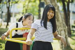 Toothy smiling face of asian teenager relaxing in children playground stock photos