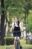 Toothy smiling face of asian teenager riding bicycle in green pa Royalty Free Stock Image
