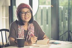 Toothy smiling face of asian woman reading pocket book in coffee. Shop Royalty Free Stock Photography